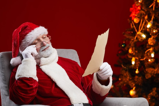 Santa claus in red costume sitting on armchair and reading a letter from a child