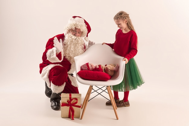 Santa claus in red costume with a little girl and a baby isolated on white