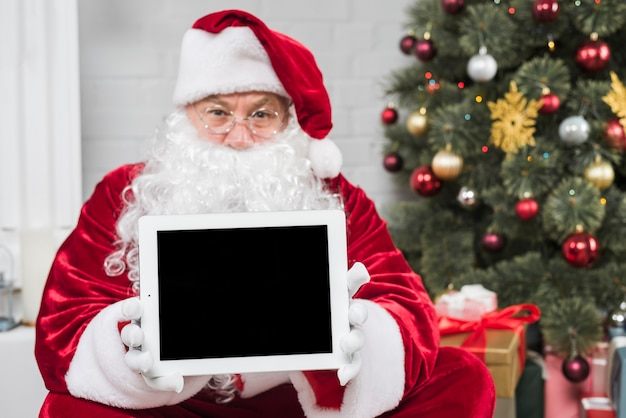 Santa claus in red hat holding tablet in hands
