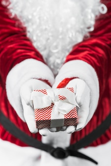 Santa claus in red holding small gift box in hands