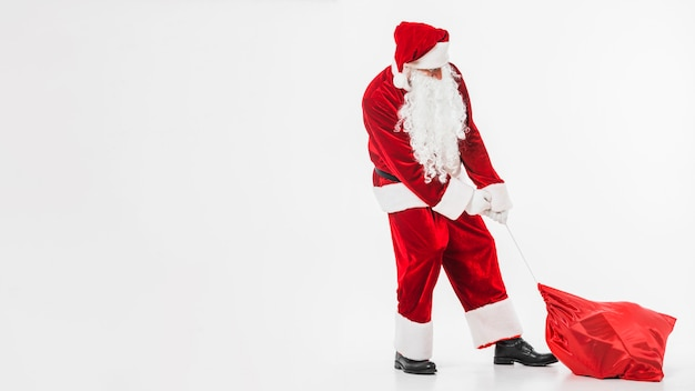 Santa claus in red pulling sack of gifts