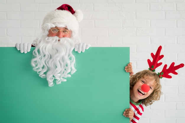 Santa claus and reindeer child holding banner blank