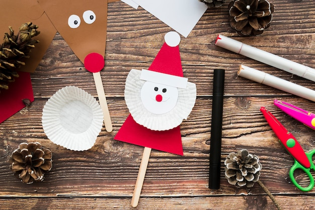 Santa claus and reindeer props with pinecones; felt-tip pen and scissor on wooden desk