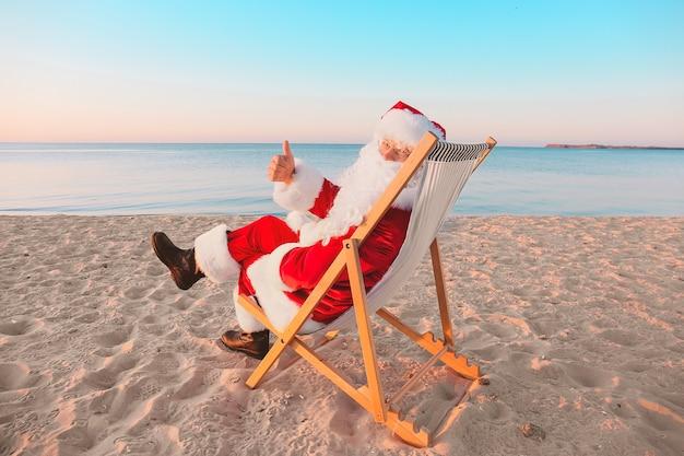 サンタ クロースが海のリゾートで休んでいます。