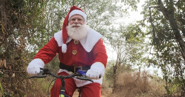 Santa claus riding a bicycle on dirt road.