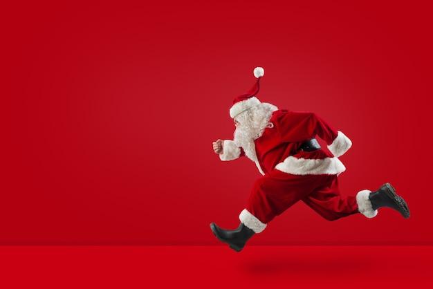 サンタクロースは赤い背景にクリスマスプレゼントを準備するために速く走ります
