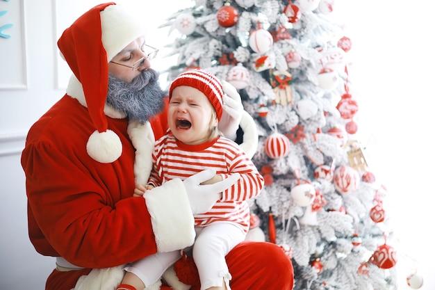 サンタクロースのヘルパー。クリスマスのために美しく装飾された部屋でクリスマスエルフの衣装を着たかわいい子供たち。奇跡の時。サンタクロースからの贈り物。