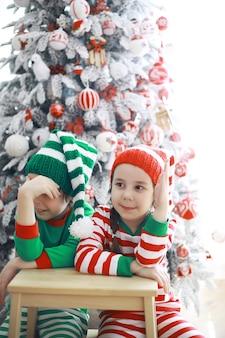 산타 클로스의 도우미입니다. 크리스마스를 위해 아름답게 장식된 방에서 크리스마스 요정 의상을 입은 귀여운 아이들. 기적의 시간. 산타클로스의 선물.
