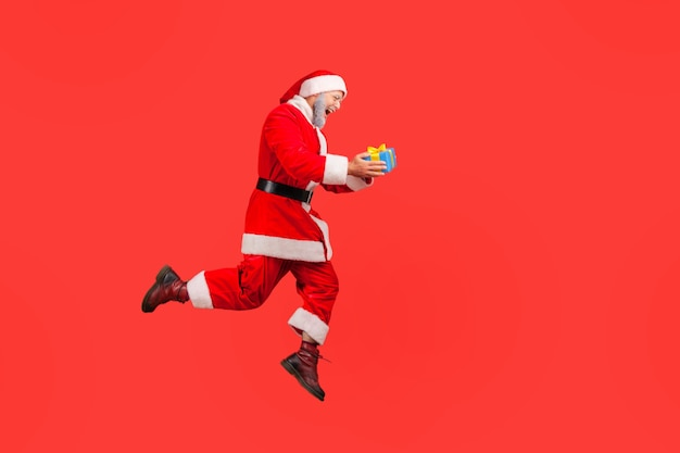 Santa claus satisfied with winter holidays, jumping high with wrapped gift box.