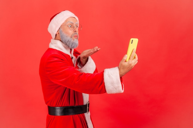 Santa claus sending air kiss to followers while broadcasting livestream or making selfie.