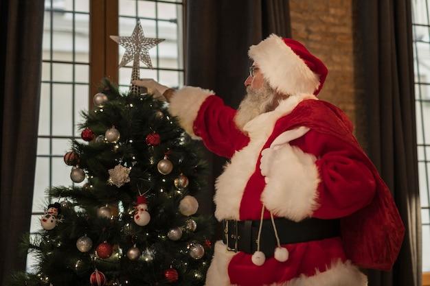 Santa claus setting up christmas tree
