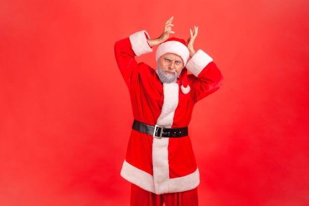 머리 위로 사슴뿔 뿔을 보여주는 산타클로스는 코믹한 유머러스한 표정을 지으며 찾고 있습니다.