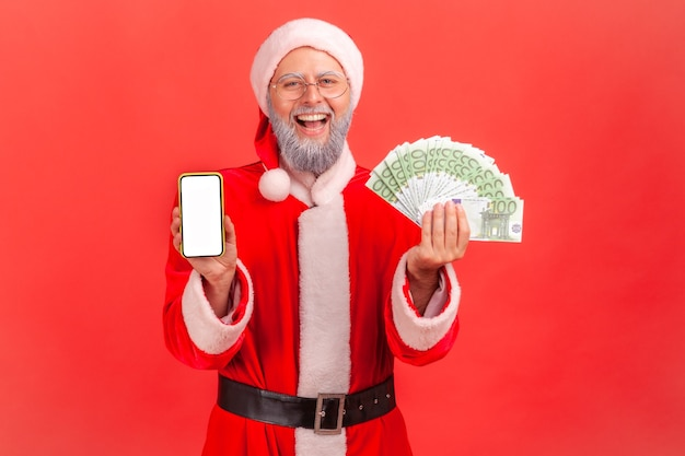Santa claus showing euro banknotes and smartphone with blank white screen.