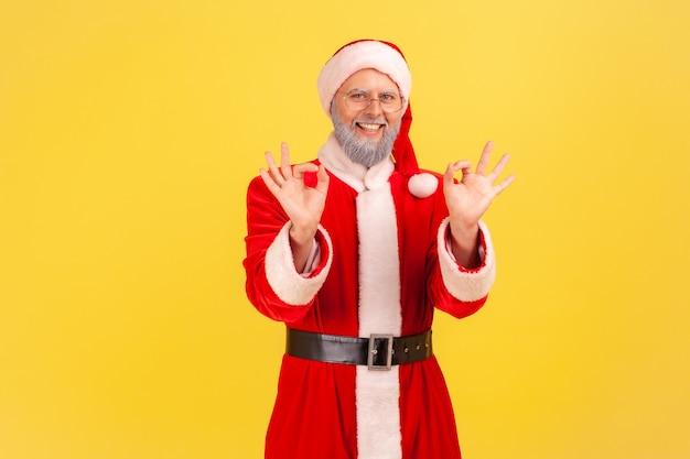두 손으로 괜 찮 아 요 기호를 보여주는 산타 클로스 카메라 이빨 미소를 찾고.