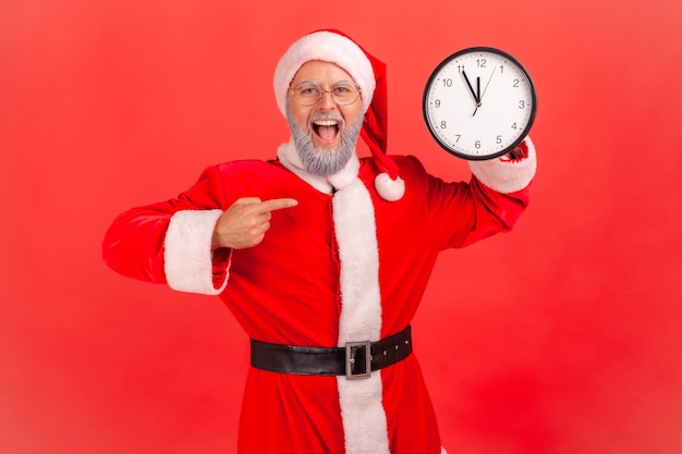 Santa claus showing pointing at wall clock, keeping mouth open, amazing look.