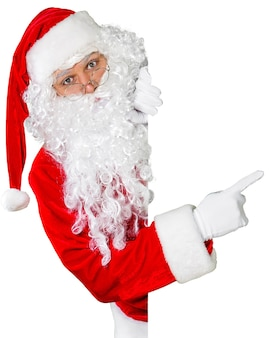 Santa claus showing something on a white wall