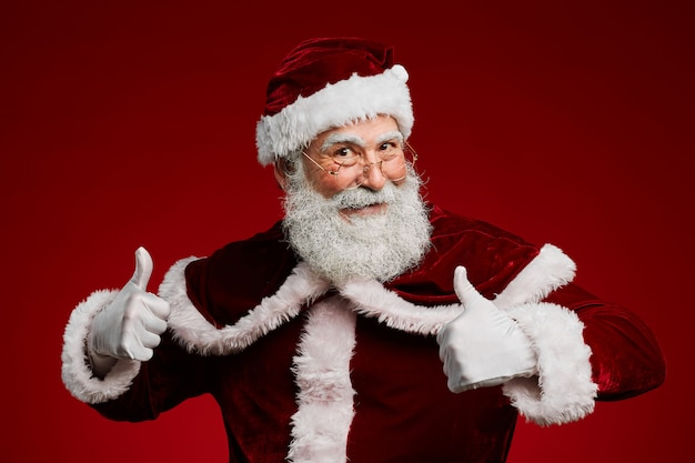 Santa claus showing thumbs up on red