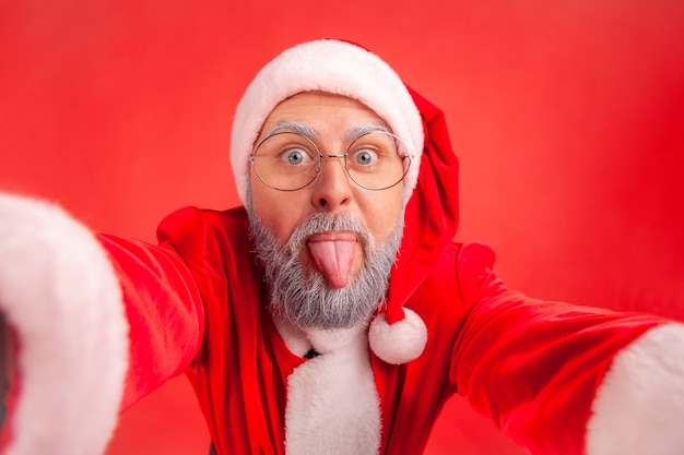 Santa claus showing tongue out while making selfie point of view photo, positive emotions.