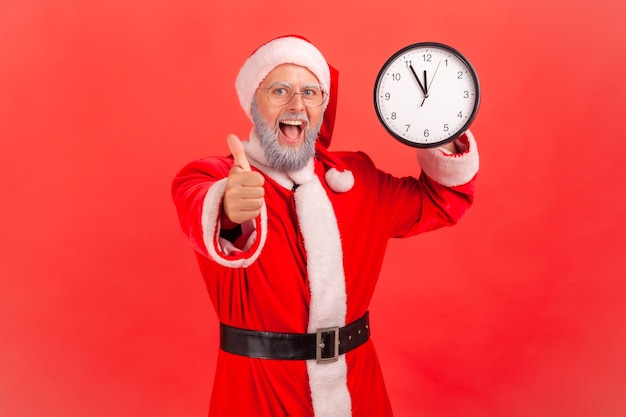 Santa claus showing wall clock and pointing finger to camera, has amazed expression.