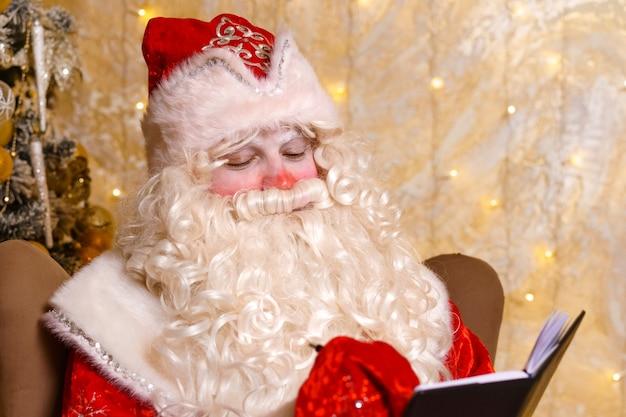 산타클로스는 크리스마스 트리 배경의 의자에 앉아 노트북에 글을 씁니다.