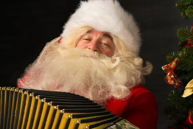 Santa claus sitting in armchair at home and playing music on accordion. christmas party merritment