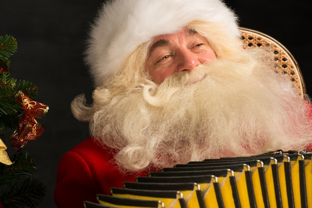 Santa claus sitting in armchair at home and playing music on accordion