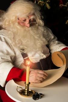 Санта-клаус сидит дома и пишет письмо