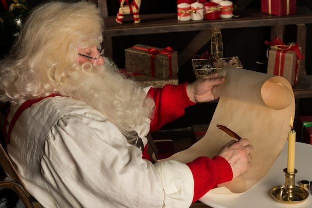산타 클로스는 집에 앉아 깃털 펜과 잉크로 목록을 작성하는 오래 된 종이 롤에 쓰기