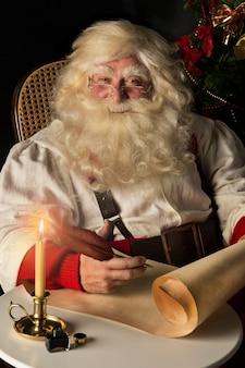 Санта-клаус сидит дома и пишет на старой бумажной рулоне, чтобы сделать список с пером