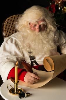 산타 클로스 집에 앉아서 퀼 펜으로 목록을 작성하는 오래 된 종이 롤에 쓰기