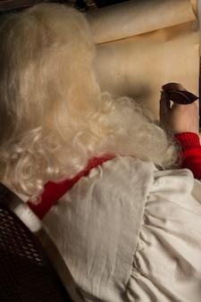 산타 클로스 집에 앉아서 오래 된 종이 롤에 쓰기