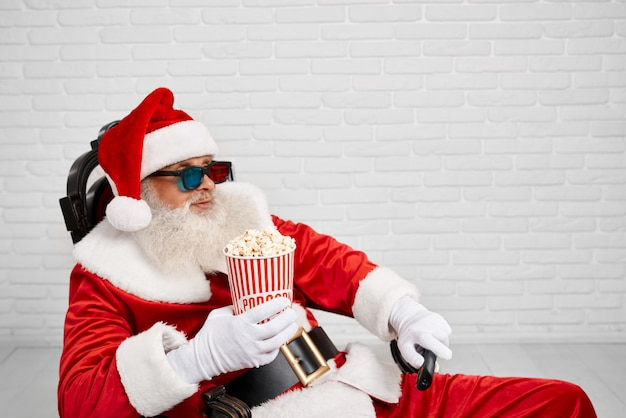 Santa claus sitting in chair with popcorn and tv zapper