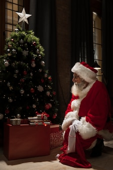 Santa claus sitting next to christmas tree