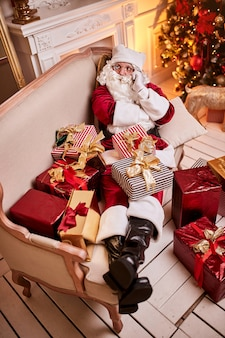 Santa claus sitting on couch and talking on mobile phone near the fireplace and christmas tree with gifts.