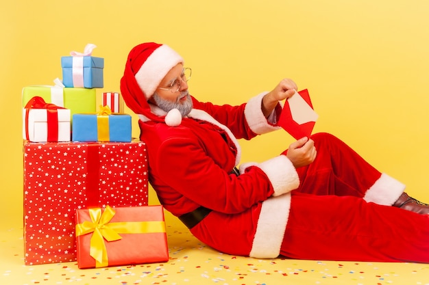 Santa claus sitting on floor near present boxes, reading letter with christmas congratulations.