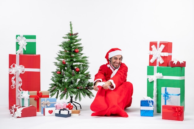 Santa claus sitting in the ground and holding christmas sock near gifts and decorated tree