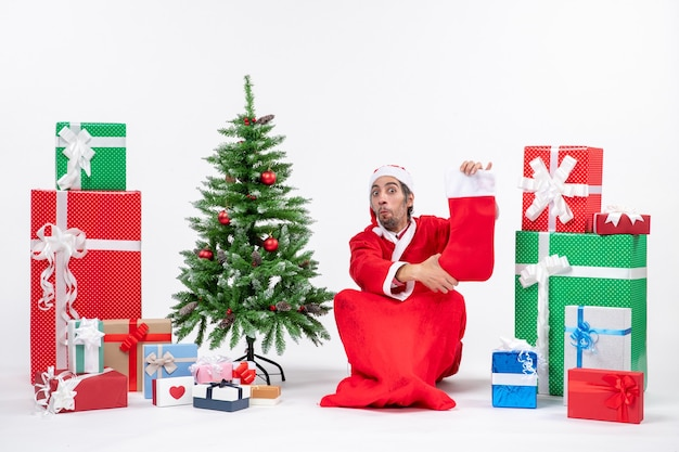Santa claus sitting in the ground and holding christmas sock near gifts and decorated xmas tree