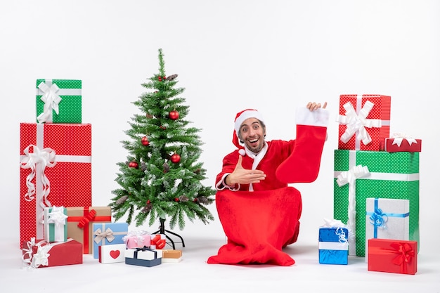 Santa claus sitting in the ground and pointing christmas sock near gifts and decorated xmas tree