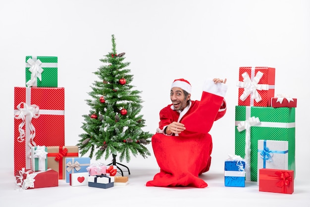 Santa claus sitting in the ground and showing christmas sock near gifts and decorated xmas tree
