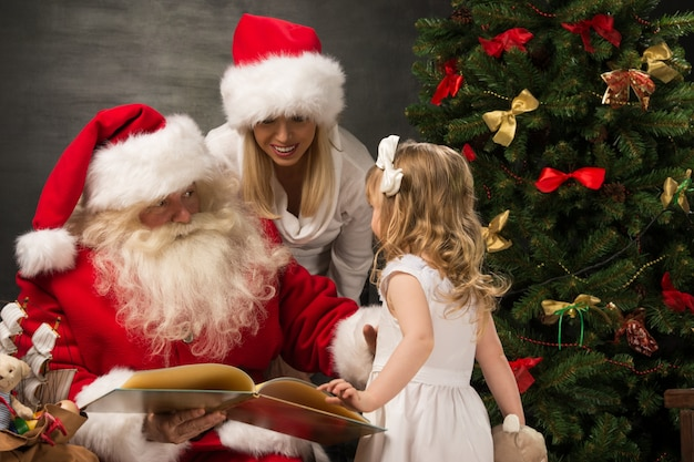Santa claus sitting at home with family - little girl and her mother and reading book all together