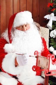 산타 클로스는 편안한 흔들 의자에 앉아 집에서 크리스마스 근처에 선물을 장식했습니다.