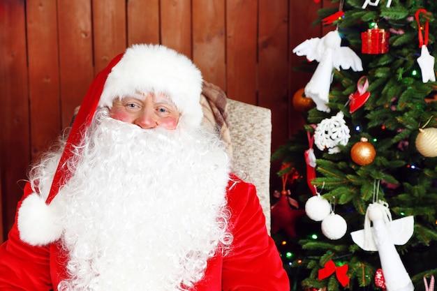 Санта-клаус сидит в удобном кресле-качалке возле рождества у себя дома