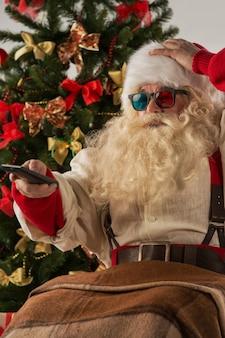 Санта-клаус сидит в кресле-качалке возле рождественской елки