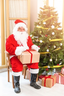 Santa claus sitting near christmas tree with present