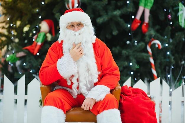 モールのクリスマスツリーの近くの椅子に座っているサンタクロース