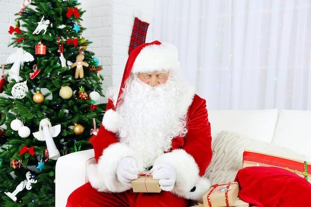 산타 클로스는 크리스마스 트리 근처 선물 상자와 함께 소파에 앉아