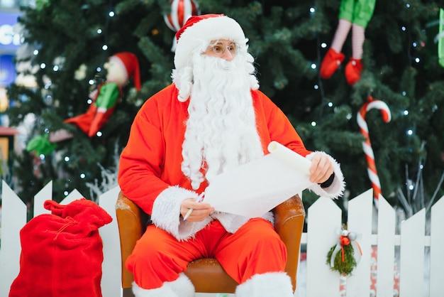 Санта-клаус сидит на фоне елки в холле современного торгового центра. боке основной фон для дизайна.