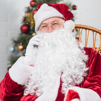 Santa claus sitting on rocking chair and talking by phone