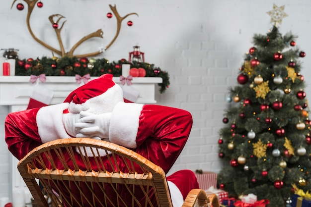 Santa claus sitting on rocking chair with hands behind head
