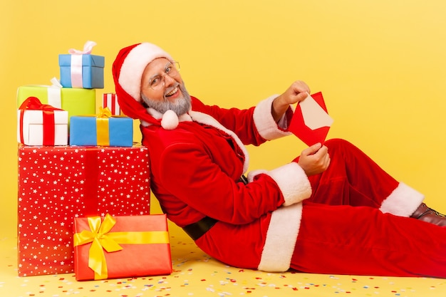 Santa claus sitting surrounded with christmas boxes, holding envelope and smiling to camera.